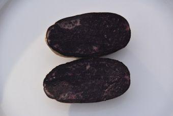 La pomme de terre 'Violet Queen' cru coupée en deux.